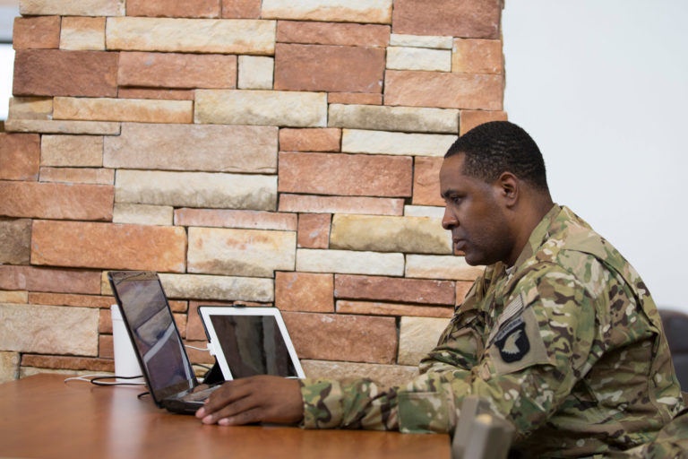 student in uniform at laptop
