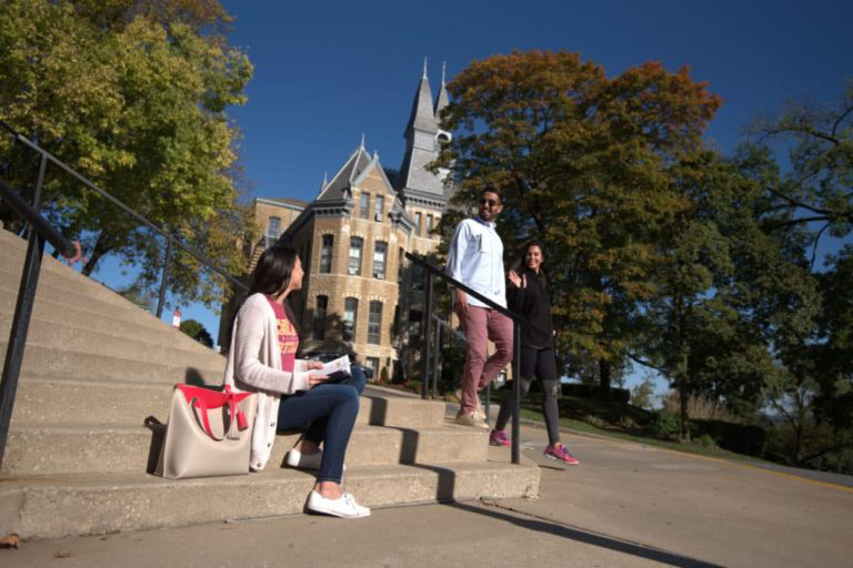 students on steps in front of campus building